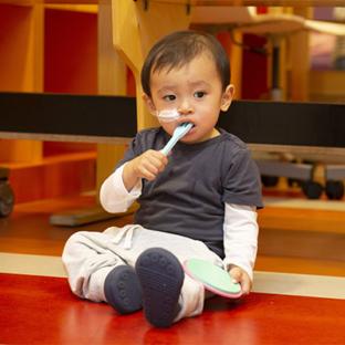 Een foto van een jong jongetje met iets in zijn mond